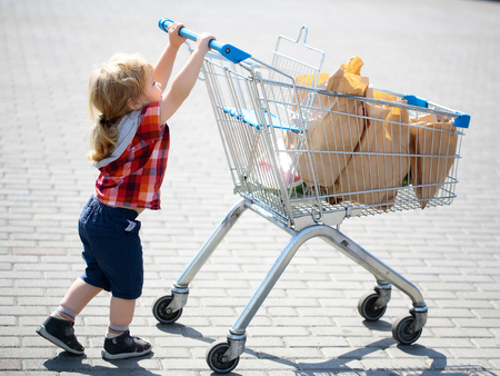 niño empujando: Cute baby boy blond child in plaid shirt pushing shopping trolley with paper packet outdoors on sunny day Foto de archivo