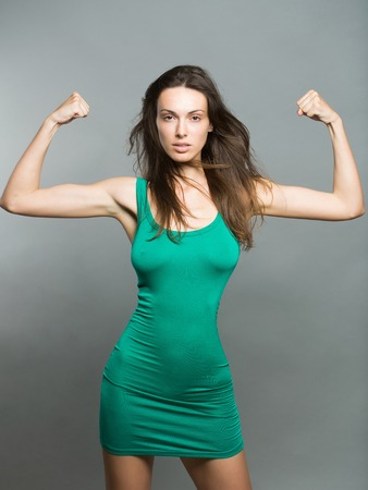 Pretty brunette woman in tight green dress on slim body showing muscularity on gray studio background