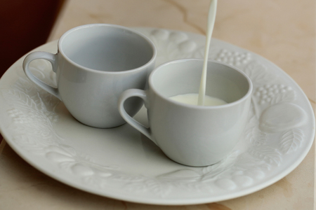 pasteurized: Pouring milk in pair of cups on white plate for breakfast on beige background