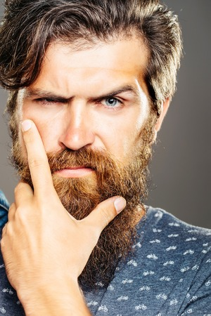 eyebrow raised: Handsome man serious hipster with long beard moustache and raised eyebrow on grey background Stock Photo