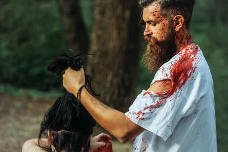 young halloween couple of bearded man with beard and sexy pretty girl with long hair and red blood as traditional autumn holiday symbol outdoor in deep green forest or wood
