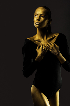face cloth: sexy golden slim woman or girl has pretty face with makeup and body art metallized color in black cloth on dark background
