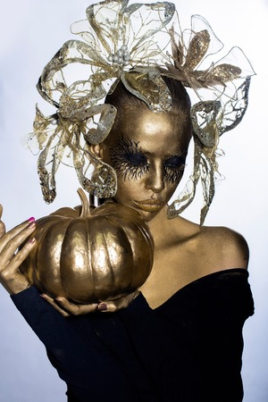 cinderella pumpkin: halloween golden woman or girl holding painted gold pumpkin has pretty face with makeup and body art metallized color with decorative flowers on head on white grey background