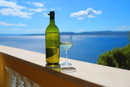 bocal: alcoholic beverage of white wine in green bottle and glass outdoor on summer day on blue sea