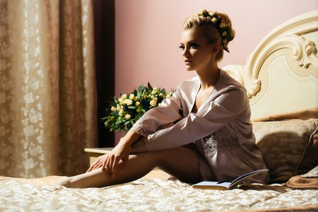 negligee: Beautiful woman sensual young bride with wreath in elegant hairstyle in sexy silk negligee on bed in bedroom