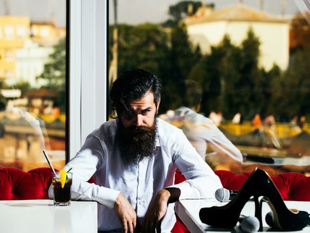 handsome bearded man with long lush beard and moustache on serious face sits between two tables with cocktail microphone and pair of shoes on them on city background