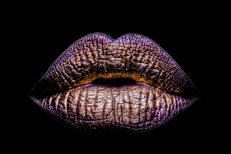female golden or gold lips isolated on black background as makeup or body art painted mouth metallized color with violet shade