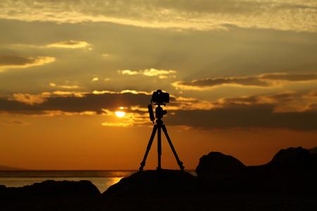 Het silhouet van de fotocamera op driepoot bij rotsachtig strand met mooie zonsondergang in blauwe overzees op zeegezichtachtergrond