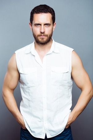 muscularity: Handsome muscularity bearded man in white shirt and jeans on gray studio background