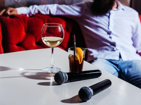 nonalcoholic: Black microphones white wine and nonalcoholic cocktail with lemon and mint in glass with transparent and black rolls on white table in front of man Stock Photo