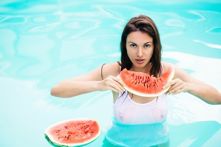 young sexy pretty brunette girl with long hair and white wet shirt on slim body eat watermelon in swimming pool with blue water in sunny summer day outdoor