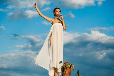 Pretty young girl or woman in white sexy dress denuded with red wine in glass wicker bottle vine and grapes on nature over blue sky