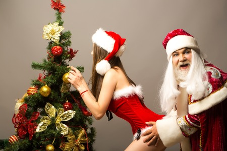 Funny santa claus man in new year suit grabs pretty sexy girl decorating Christmas tree on grey wall Stock Photo