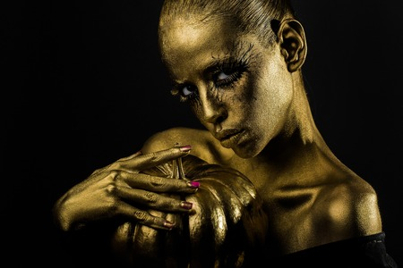 halloween golden woman or girl holding painted gold pumpkin has pretty face with makeup and body art metallized color with bare shoulders on black background Stock Photo