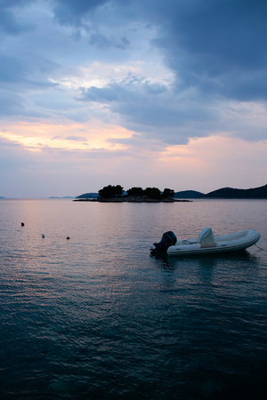 inshore: White boat inflatable rubber vessel with motor at anchor in calm blue sea water inshore after sunset on beautiful evening seascape Stock Photo