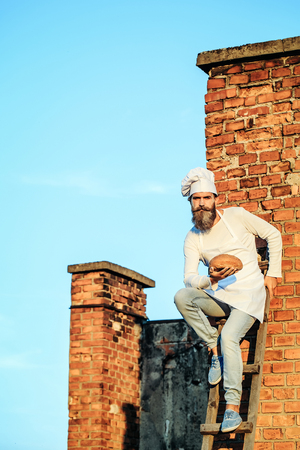Handsome bearded man cook chef in white uniform with long beard holding bread in hands on ladder on sunny day outdoor on stony wall background, copy space