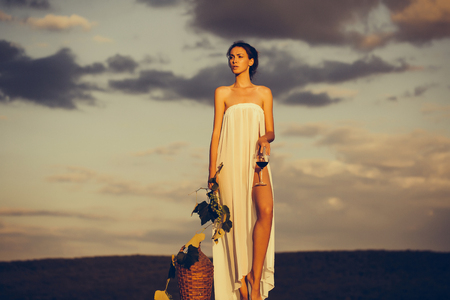 denuded: Pretty young girl or woman in white sexy dress denuded with red wine in glass wicker bottle vine and grapes on nature over sky in sunset Stock Photo