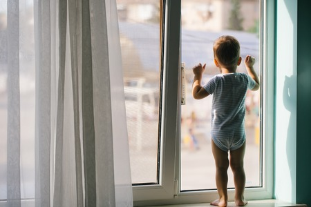 stays: Cute baby boy kid child with blond hair in striped romper stays on sill and looks at window at home