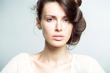 Brunette bastante sensible en la camisa blanca con el pelo recogido en el fondo gris del estudio