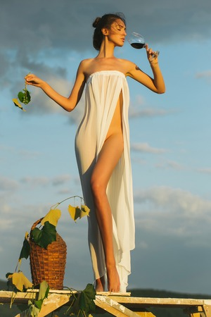 bottle of vine: Pretty young girl or woman in white sexy dress denuded with red wine in glass wicker bottle vine and grapes on nature over blue sky
