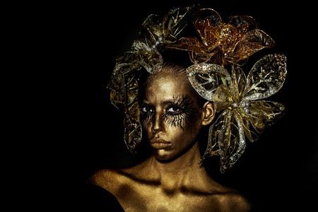 donna d'oro o una ragazza ha bel viso con trucco e body art metallizzato colore con fiori decorativi sulla testa su sfondo nero,, copia spazio Archivio Fotografico