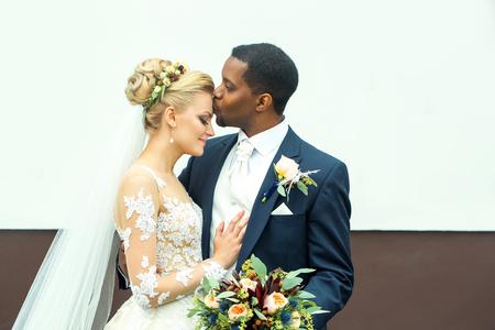 Junger Mann elegant afrikanischen amerikanischen Bräutigam küsst zärtlich schöne Frau glücklich Braut im weißen Kleid und Schleier Ehepaar am Hochzeitstag