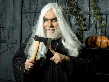 Robe: Evil old gray sorcerer in black robe with beard hold axe near finger in wooden house Stock Photo