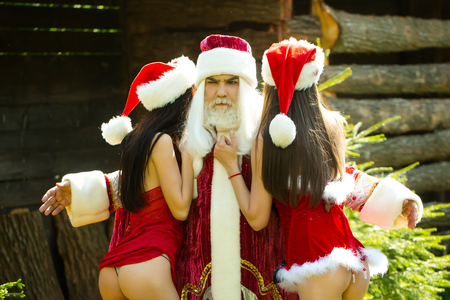 half nude: Outside celebration of Christmas with beautiful half nude ladies. Man in santa claus costume with two sexy attractive girls