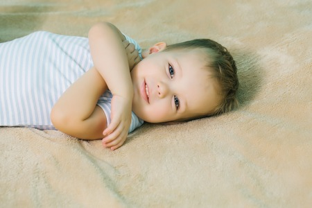 hair cover: Happy baby boy with blue eyes and blond hair in romper smiles on beige bed cover