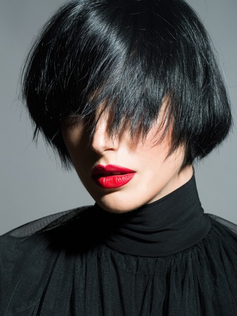 face cloth: young sexy woman or girl with short brunette stylish hair and red lips on pretty face in black cloth on grey background, closeup Stock Photo
