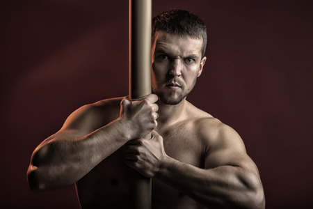 sexual anatomy: One sexual strong young man with muscular body in jeans holding iron crossbar standing posing in studio on red background, horizontal picture Stock Photo