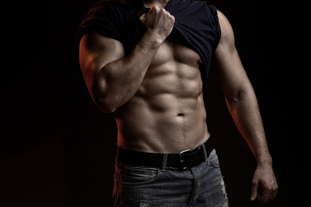 Ein hübscher sexueller starker junger Mann mit muskulösem Körper in den Blue Jeans mit dem Hemd auf der Schulter, die im Studio auf schwarzem Hintergrund, horizontales Bild aufwirft
