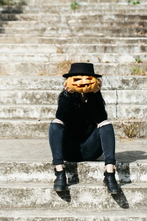 young halloween woman or girl in black witch hat and stylish jeans sitting on stony stairs with traditional autumn holiday symbol of orange spooky pumpkin outdoor