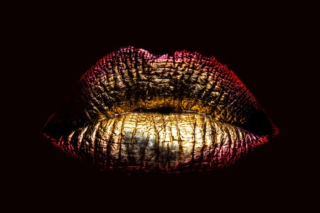 female golden or gold lips isolated on black background as makeup or body art painted mouth metallized color with red contour