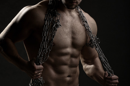 pectoral muscle: One handsome sexual strong young man with muscular body in blue jeans holding rope with hands hanging on neck and shoulders standing posing in studio on black background, horizontal picture Stock Photo