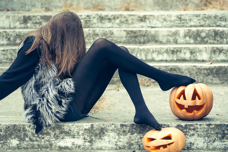 young halloween woman or girl witch with long hair in black tights and fur waistcoat sitting on stony stairs with traditional autumn holiday symbol of orange spooky pumpkin outdoor Zdjęcie Seryjne