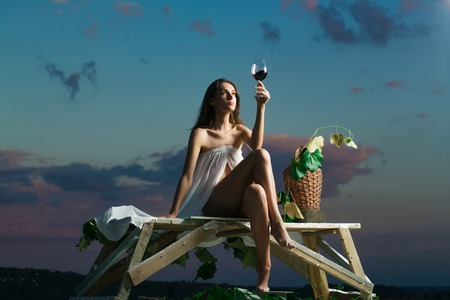 denuded: pretty girl in white sexy dress denuded gorgeous body with red wine glass wicker bottle and vine on evening nature over blue sky