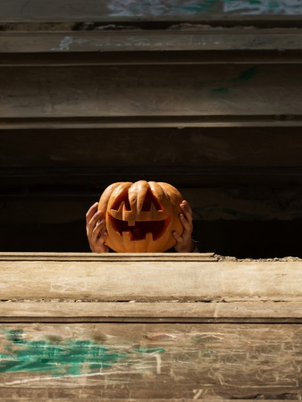 wooden railings: halloween traditional autumn holiday symbol of orange pumpkin with cut spooky face in human hands on wooden railings outdoor
