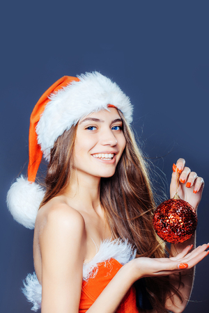 costume ball: young sexy new year woman or girl with long hair and pretty smiling, happy face in red christmas santa claus hat and holiday costume holds decorative ball in studio on grey background