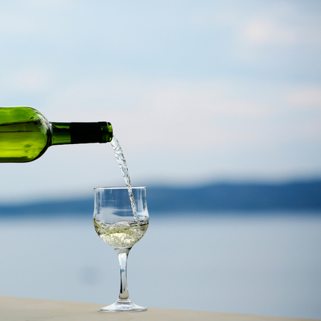 bocal: alcoholic beverage of white wine pouring from green bottle into glass outdoor on summer day on blue sea Stock Photo