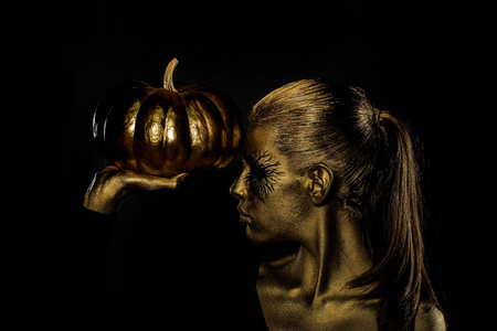 cinderella pumpkin: halloween golden woman or girl holding painted gold pumpkin has pretty face with makeup and body art metallized color on black background