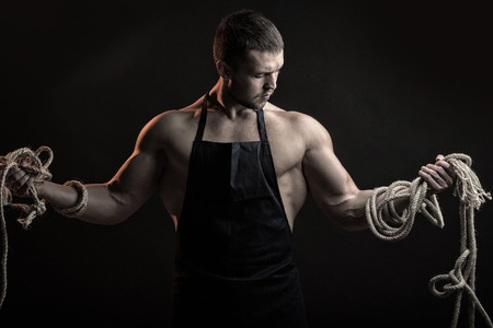 sexual anatomy: One handsome sexual strong young man with muscular body in working blue apron holding rope standing posing in studio on black background, horizontal picture