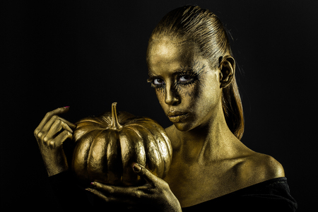 cinderella pumpkin: halloween golden woman or girl holding painted gold pumpkin has pretty face with makeup and body art metallized color with bare shoulders on black background Stock Photo