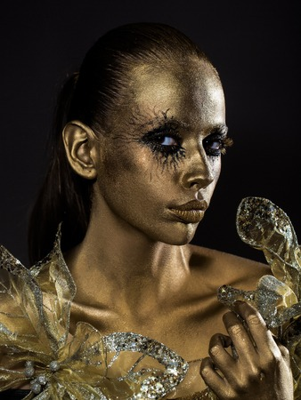 golden woman or girl has pretty face with makeup and body art metallized color with decorative flowers on black background Stock Photo