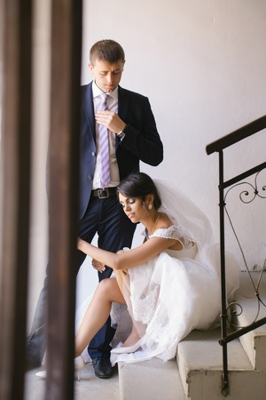 elegant staircase: Beautiful bride woman in white wedding dress and veil sits on staircase and holds leg of elegant groom man