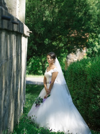 young sexy woman or girl bride with makeup on pretty face and veil in hair holding wedding bouquet or posy of eustoma and rose flowers sunny summer outdoor near stony wall on green natural background