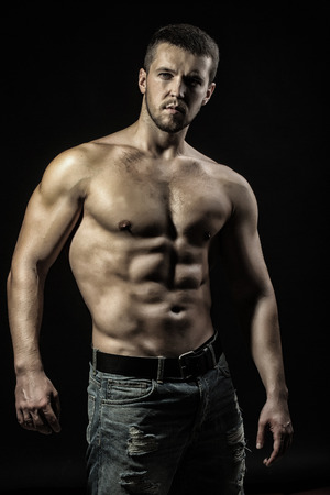 sexual anatomy: One sexual strong young man with muscular body in jeans looking forward standing posing in studio on black background, vertical picture