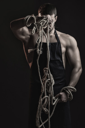 One handsome sexual strong young man with muscular body in working blue apron holding rope standing posing in studio on black background, vertical picture