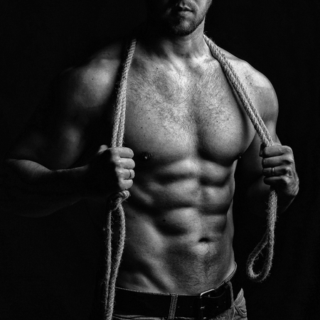 sexual anatomy: One handsome sexual strong young man with muscular body in blue jeans holding rope with hands hanging on neck and shoulders standing posing in studio black and white, square picture Stock Photo