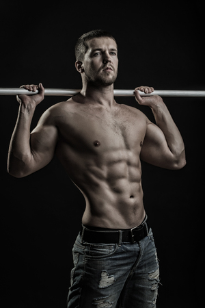 One sexual strong young man with muscular body in jeans holding iron crossbar standing posing in studio on black background, vertical picture
